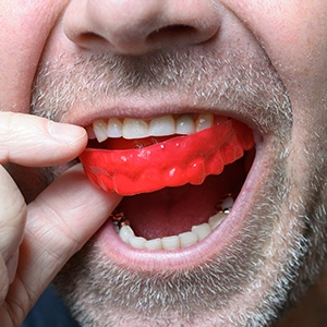 man putting in red mouthguard