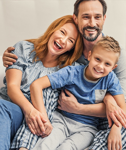 family of three laughing and smiling