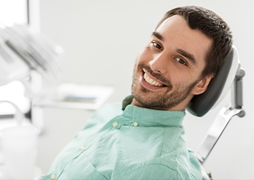 man in green shirt smiling in exam chair