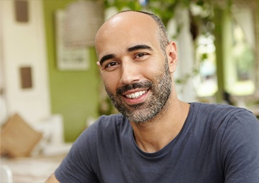 man in gray shirt with beard smiling