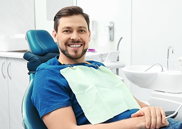 man with blue shirt smiling in exam chair