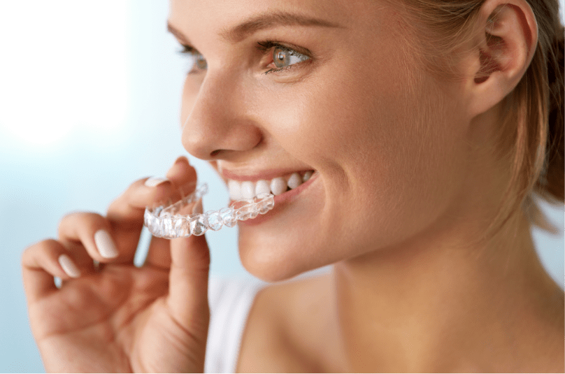 woman smiling putting in invisalign