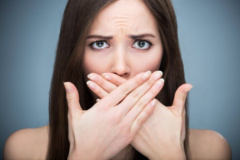 Concerned woman covering her mouth