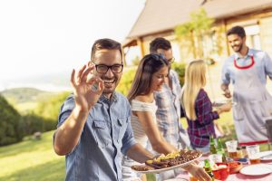 Man at barbeque eating with dentures